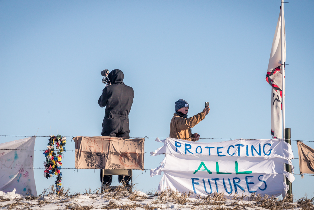People recording the incoming traffic to Oceti Sakowin