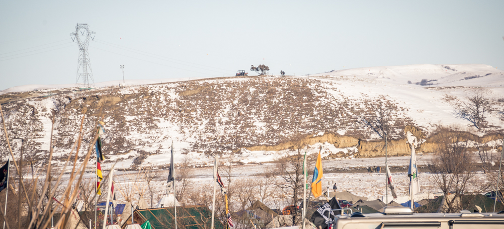 Two figures and an ATV on the hill overlooking Oceti Sakowin